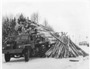 40's truck with dumped load of long logs