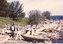 "Hank Emerson; note the ""dri-Ki"" or drift wood on shore. Taken in front of Kenneson's. Hank is at the right. 1957 3 HP Johnson and Old Town Lapstrake."